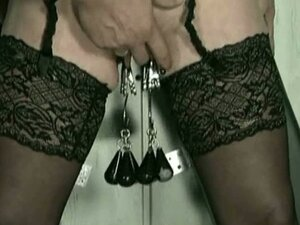 Beautiful slave with metal clamps on her pussy