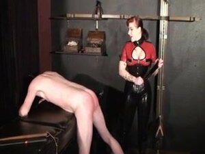 Redhead dominatrix in latex tortures her thrall,