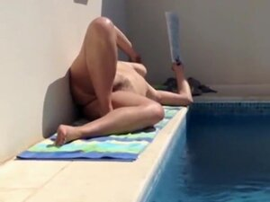 Mature lady relaxes nude by the pool, I filmed