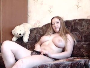Chubby redhead plays solo on the couch,