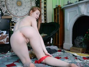 Petite redhead stretches with a giant dildo