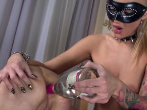 Masked mistress inserts a bottle in her slave's